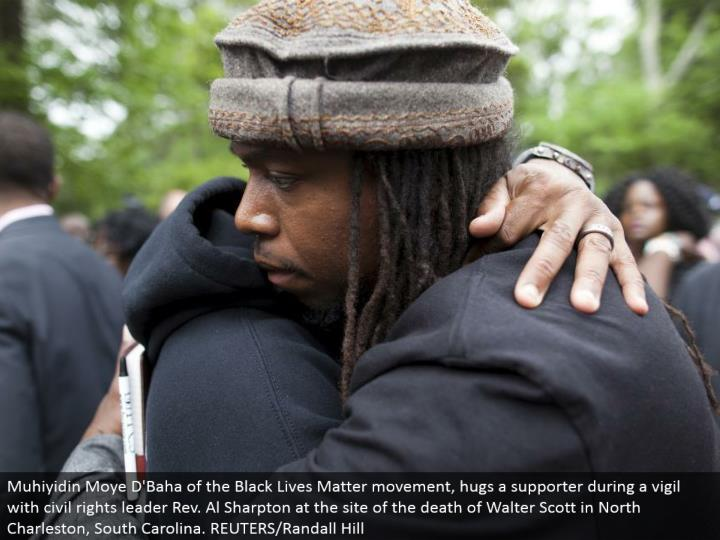Muhiyidin Moye D'Baha of the Black Lives Matter advancement, grasps a supporter in the midst of a vigil with social freedoms pioneer Rev. Al Sharpton at the site of the death of Walter Scott in North Charleston, South Carolina. REUTERS/Randall Hill
