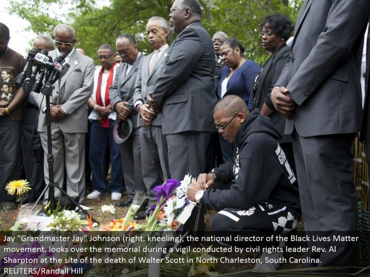 "Jay ""Grandmaster Jay"" Johnson (right, bowing), the national official of the Black Lives Matter improvement, explores the recognition in the midst of a vigil coordinated by social freedoms pioneer Rev. Al Sharpton at the site of the death of Walter Scott in North Charleston, South Carolina. REUTERS/Randall Hill"