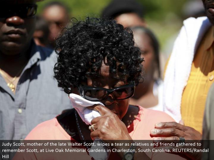 Judy Scott, mother of the late Walter Scott, wipes a tear as relatives and associates collected to review Scott, at Live Oak Memorial Gardens in Charleston, South Carolina. REUTERS/Randal Hill