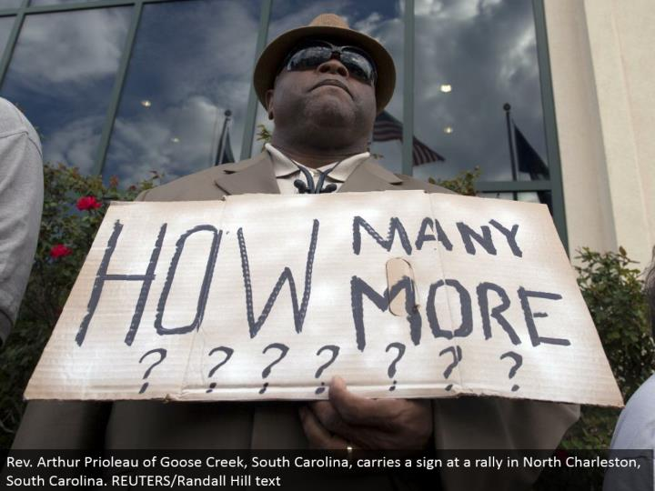 Rev. Arthur Prioleau of Goose Creek, South Carolina, passes on a sign at a rally in North Charleston, South Carolina. REUTERS/Randall Hill text