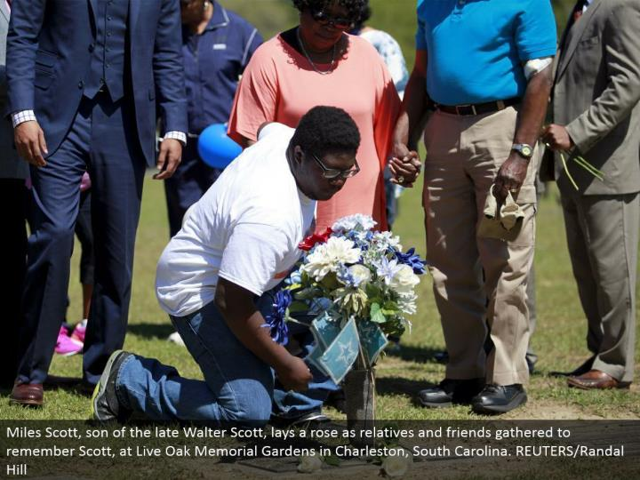Miles Scott, offspring of the late Walter Scott, lays a rose as relatives and sidekicks gathered to review Scott, at Live Oak Memorial Gardens in Charleston, South Carolina. REUTERS/Randal Hill