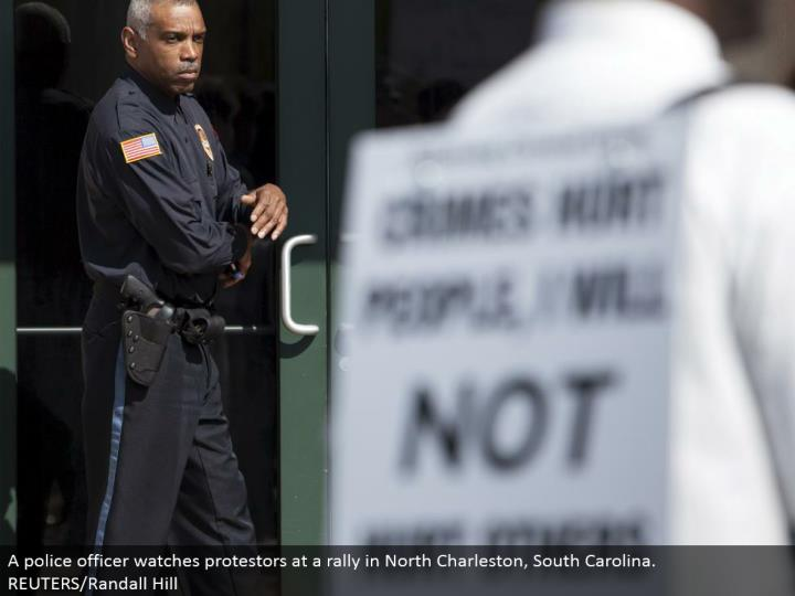 A cop watches protestors at a rally in North Charleston, South Carolina. REUTERS/Randall Hill