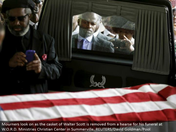 Mourners look on as the casket of Walter Scott is ousted from a memorial service auto for his internment benefit at W.O.R.D. Administrations Christian Center in Summerville. REUTERS/David Goldman/Pool