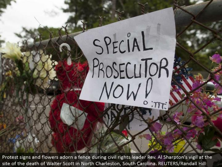 Protest signs and blooms embellish a fence in the midst of social freedoms pioneer Rev. Al Sharpton's vigil at the site of the death of Walter Scott in North Charleston, South Carolina. REUTERS/Randall Hill