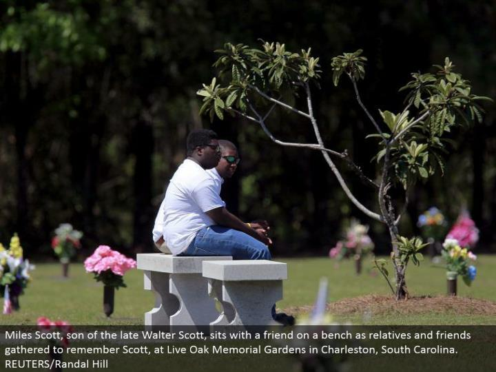 Miles Scott, offspring of the late Walter Scott, sits with a partner on a seat as relatives and colleagues collected to remember Scott, at Live Oak Memorial Gardens in Charleston, South Carolina. REUTERS/Randal Hill