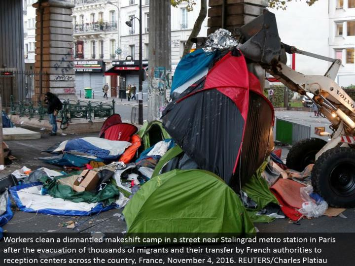 Workers clean a disassembled stopgap camp in a road close Stalingrad metro station in Paris after th...