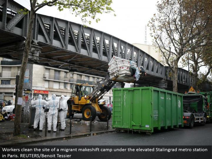 Workers clean the site of a vagrant alternative camp under the raised Stalingrad metro station in Paris. REUTERS/Benoit Tessier