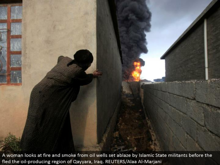 A lady takes a gander at flame and smoke from oil wells set on fire by Islamic State aggressors befo...