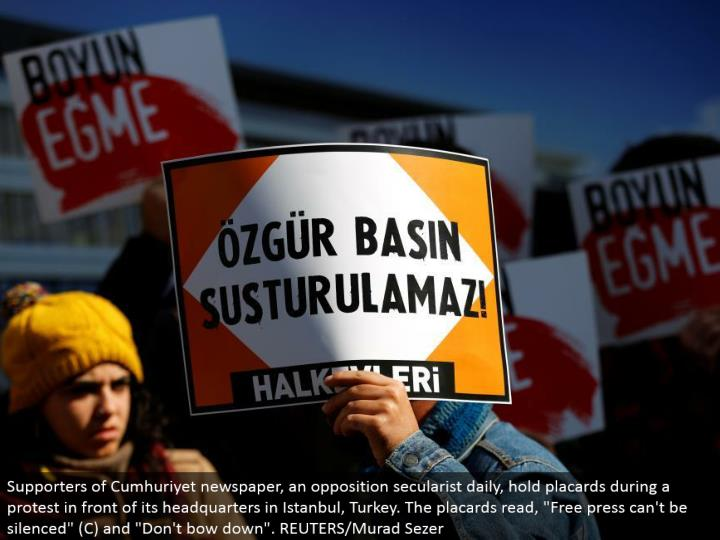"Supporters of Cumhuriyet daily paper, a restriction secularist day by day, hold bulletins amid a dissent before its central command in Istanbul, Turkey. The notices read, ""Free press can't be quieted"" (C) and ""Don't bow down"". REUTERS/Murad Sezer"