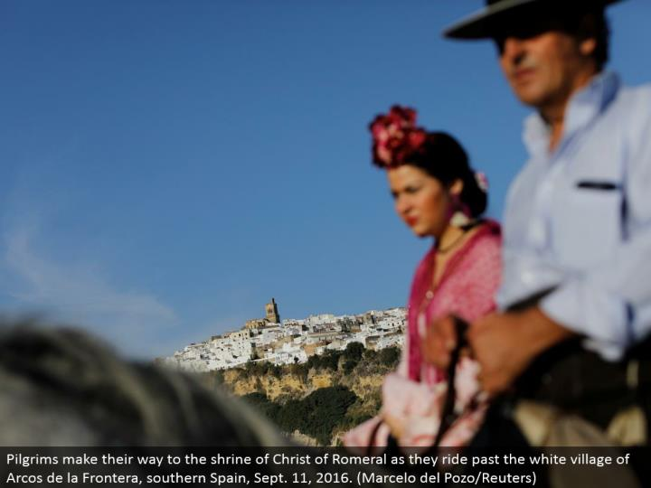 Pilgrims advance toward the hallowed place of Christ of Romeral as they ride past the white town of ...