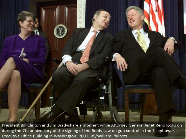 President Bill Clinton and Jim Bradyshare a minute while Attorney General Janet Reno looks on amid the seventh commemoration of the marking of the Brady Law on firearm control in the Eisenhower Executive Office Building in Washington. REUTERS/William Philpott