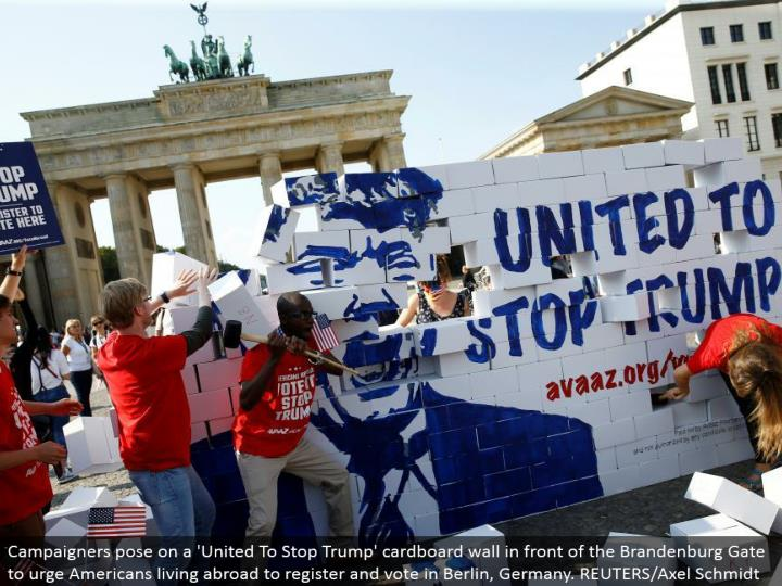 Campaigners posture on a 'Joined To Stop Trump' cardboard divider before the Brandenburg Gate to urge Americans living abroad to enroll and vote in Berlin, Germany. REUTERS/Axel Schmidt