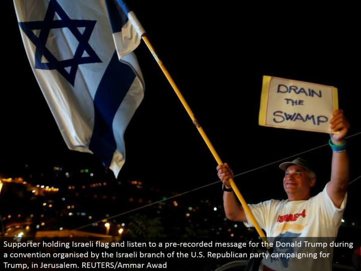 Supporter holding Israeli banner and listen to a pre-recorded message for the Donald Trump amid a tradition sorted out by the Israeli branch of the U.S. Republican gathering crusading for Trump, in Jerusalem. REUTERS/Ammar Awad