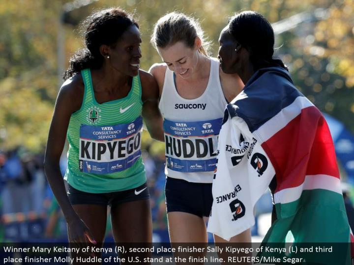 Winner Mary Keitany of Kenya (R), second place finisher Sally Kipyego of Kenya (L) and third place finisher Molly Huddle of the U.S. remain toward the complete line. REUTERS/Mike Segar