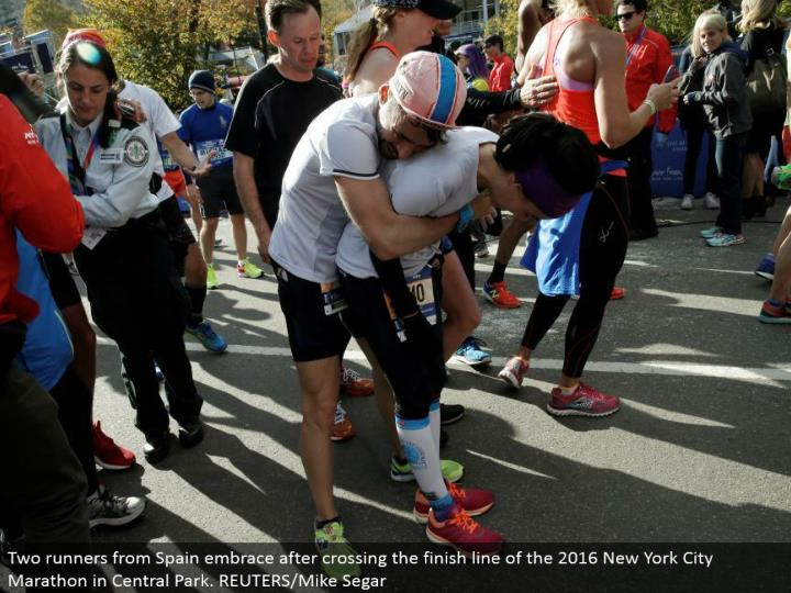 Two runners from Spain grasp in the wake of intersection the complete line of the 2016 New York City Marathon in Central Park. REUTERS/Mike Segar