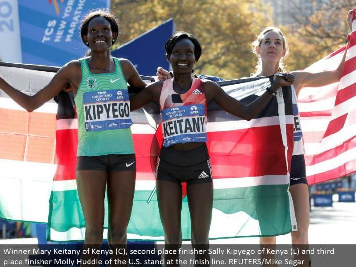 Winner Mary Keitany of Kenya (C), second place finisher Sally Kipyego of Kenya (L) and third place finisher Molly Huddle of the U.S. remain toward the complete line. REUTERS/Mike Segar