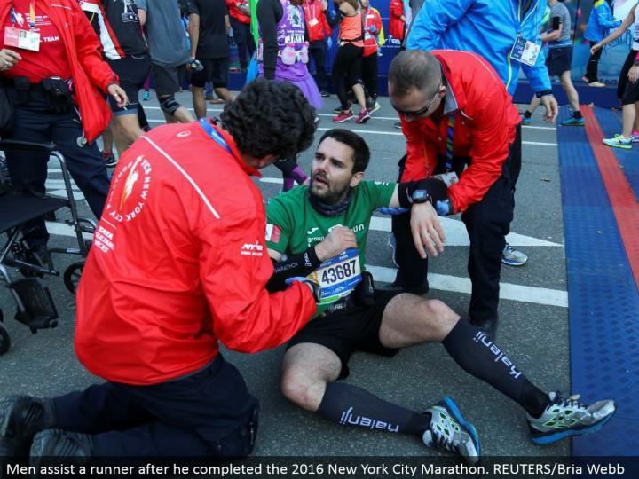 Men help a runner after he finished the 2016 New York City Marathon. REUTERS/Bria Webb