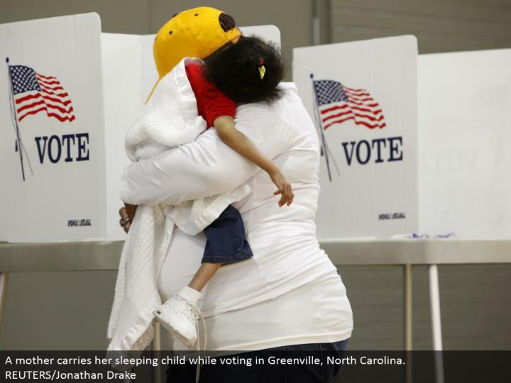 A mother conveys her resting kid while voting in Greenville, North Carolina. REUTERS/Jonathan Drake