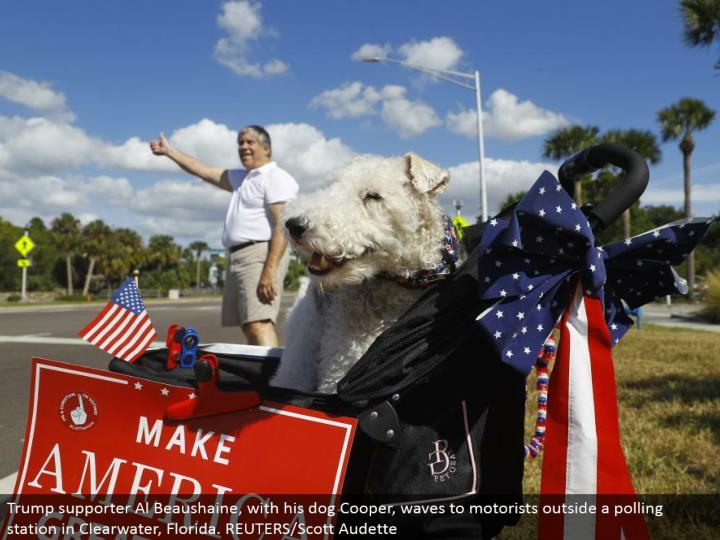 Trump supporter Al Beaushaine, with his pooch Cooper, waves to drivers outside a surveying station in Clearwater, Florida. REUTERS/Scott Audette