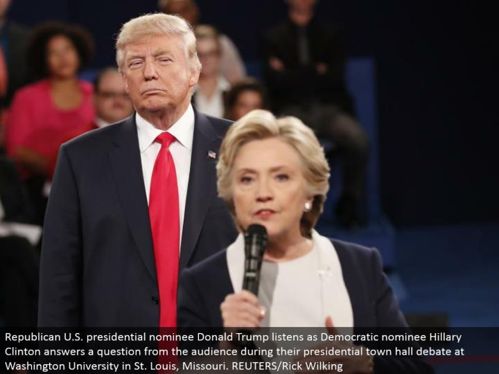 Republican U.S. presidential chosen one Donald Trump listens as Democratic candidate Hillary Clinton answers a question from the group of onlookers amid their presidential town lobby banter at Washington University in St. Louis, Missouri. REUTERS/Rick Wilking