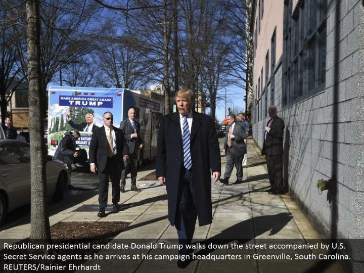 Republican presidential applicant Donald Trump strolls down the road joined by U.S. Mystery Service operators as he touches base at his battle central station in Greenville, South Carolina. REUTERS/Rainier Ehrhardt