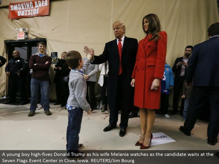 A young man high-fives Donald Trump as his better half Melania looks as the applicant holds up at the Seven Flags Event Center in Clive, Iowa. REUTERS/Jim Bourg