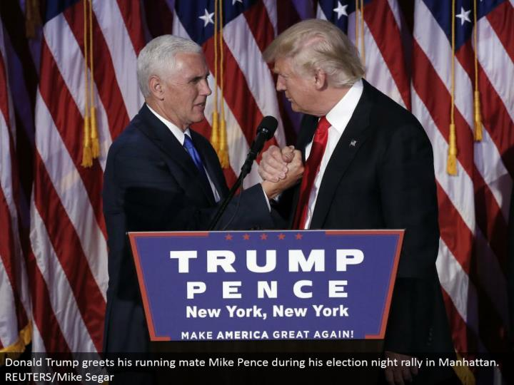 Donald Trump welcomes his running mate Mike Pence amid his race night rally in Manhattan. REUTERS/Mike Segar