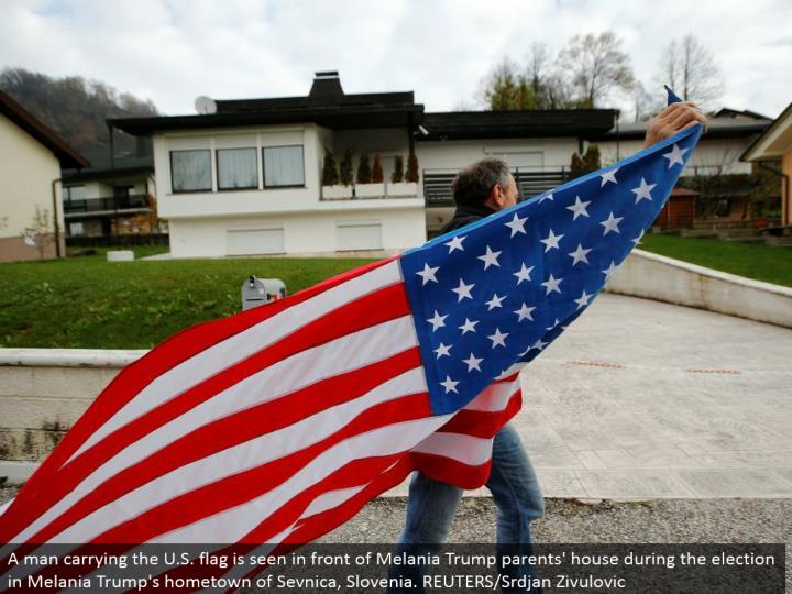 A man conveying the U.S. banner is found before Melania Trump guardians' home amid the race in Melania Trump's main residence of Sevnica, Slovenia. REUTERS/Srdjan Zivulovic