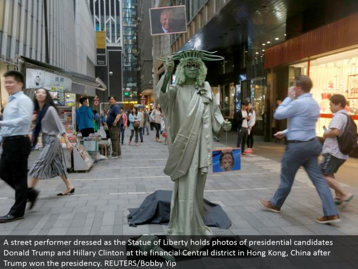 A road entertainer dressed as the Statue of Liberty holds photographs of presidential applicants Donald Trump and Hillary Clinton at the monetary Central locale in Hong Kong, China after Trump won the administration. REUTERS/Bobby Yip