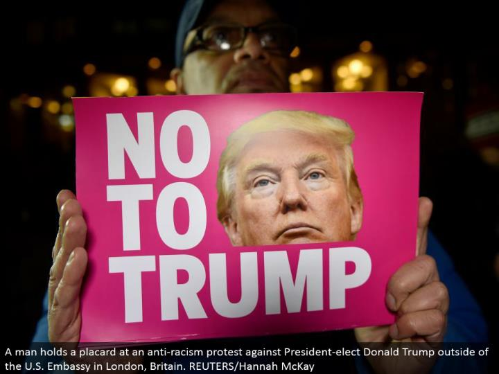 A man holds a bulletin at a hostile to bigotry challenge President-choose Donald Trump outside of th...