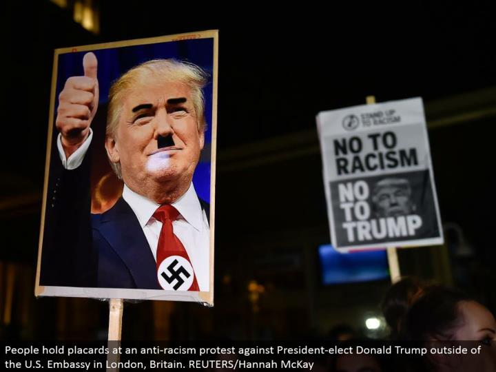 People hold bulletins at a hostile to prejudice challenge President-choose Donald Trump outside of the U.S. International safe haven in London, Britain. REUTERS/Hannah McKay