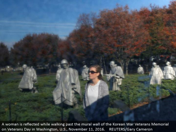 A lady is reflected while strolling past the painting mass of the Korean War Veterans Memorial on Veterans Day in Washington, U.S., November 11, 2016. REUTERS/Gary Cameron