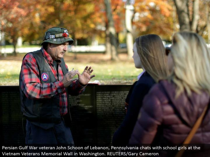 Persian Gulf War veteran John Schoon of Lebanon, Pennsylvania talks with school young ladies at the Vietnam Veterans Memorial Wall in Washington. REUTERS/Gary Cameron