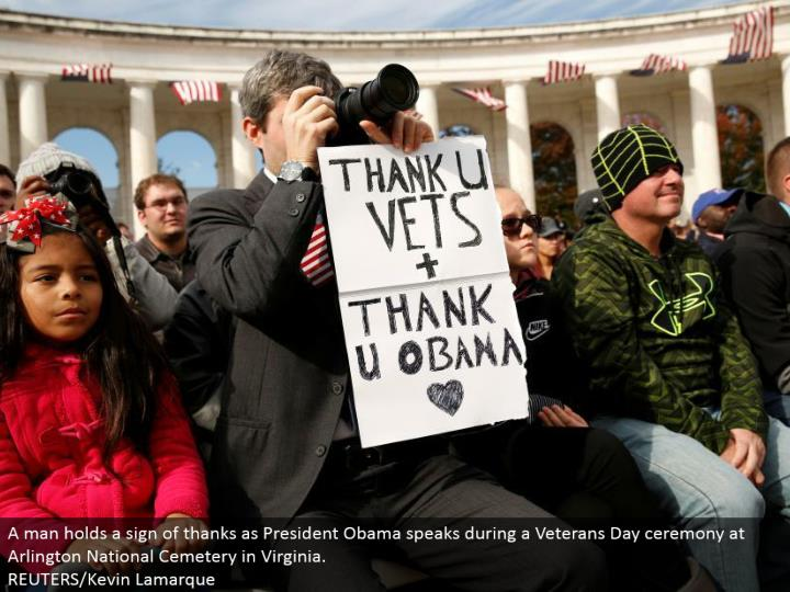 A man holds an indication of thanks as President Obama talks amid a Veterans Day service at Arlington National Cemetery in Virginia. REUTERS/Kevin Lamarque