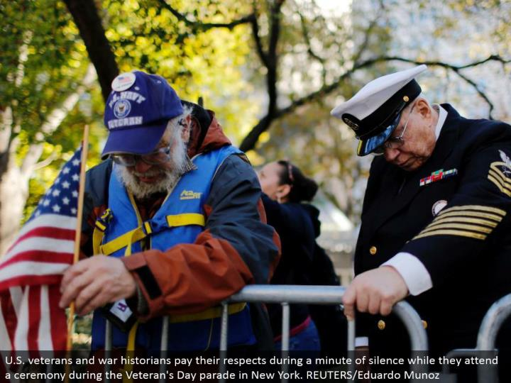 U.S. veterans and war history specialists offer their regards amid a moment of hush while they go to a function amid the Veteran's Day parade in New York. REUTERS/Eduardo Munoz