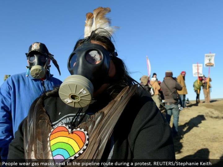 People wear gas veils alongside the pipeline course amid a dissent. REUTERS/Stephanie Keith