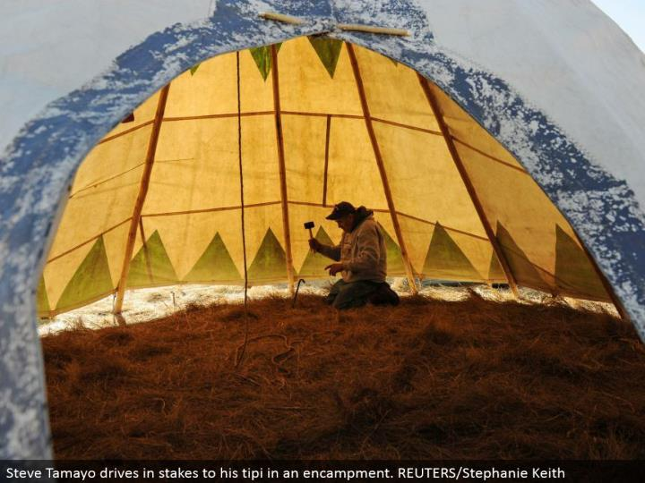 Steve Tamayo drives in stakes to his tipi in a camp. REUTERS/Stephanie Keith