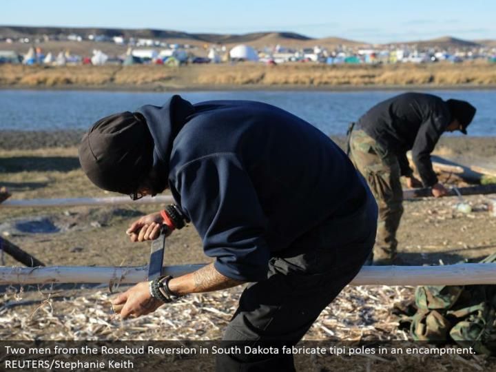 Two men from the Rosebud Reversion in South Dakota create tipi shafts in a camp. REUTERS/Stephanie Keith