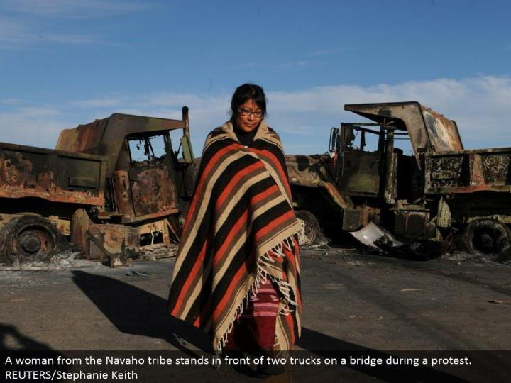 A lady from the Navaho tribe remains before two trucks on an extension amid a challenge. REUTERS/Stephanie Keith