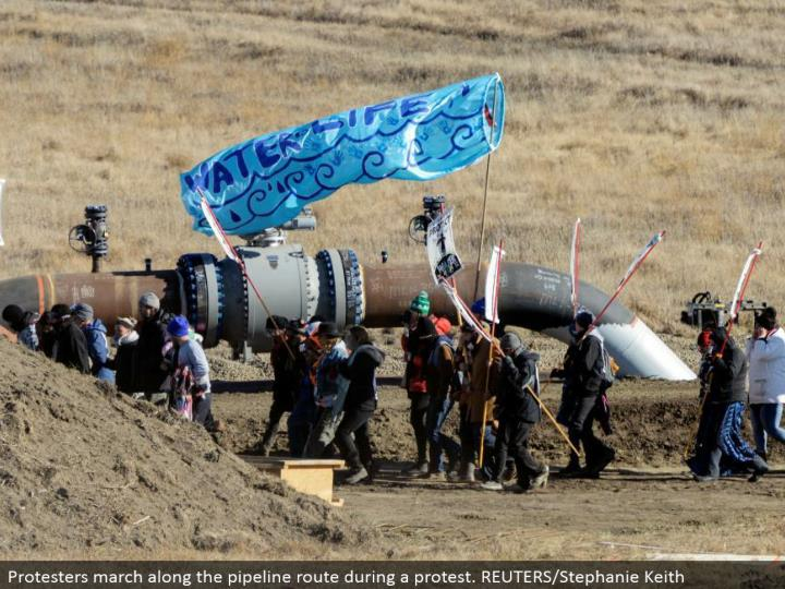 Protesters walk along the pipeline course amid a dissent. REUTERS/Stephanie Keith