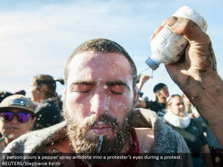 A individual empties a pepper shower counteractant into a dissenter's eyes amid a challenge. REUTERS/Stephanie Keith