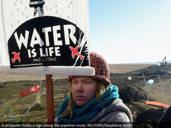 A nonconformist holds a sign along the pipeline course. REUTERS/Stephanie Keith