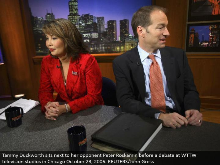 Tammy Duckworth sits beside her rival Peter Roskamin before an open deliberation at WTTW TV studios in Chicago October 23, 2006. REUTERS/John Gress