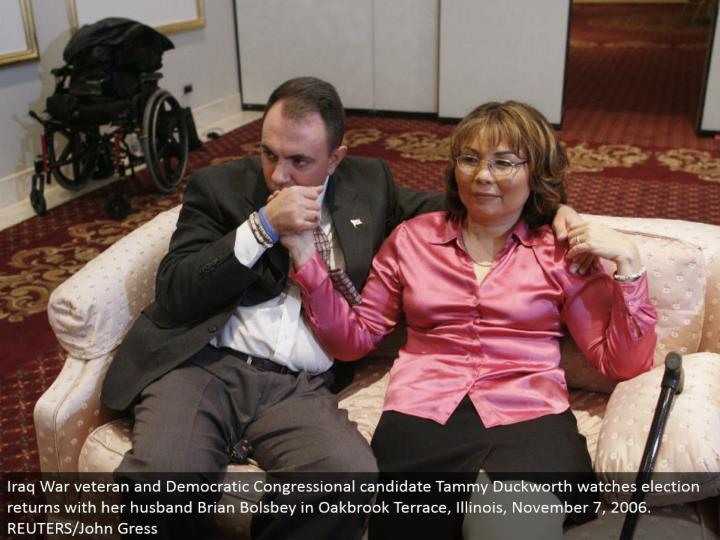 Iraq War veteran and Democratic Congressional hopeful Tammy Duckworth watches race comes back with her better half Brian Bolsbey in Oakbrook Terrace, Illinois, November 7, 2006. REUTERS/John Gress