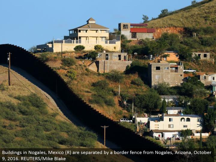 Buildings in Nogales, Mexico (R) are isolated by an outskirt fence from Nogales, Arizona, October 9, 2016. REUTERS/Mike Blake