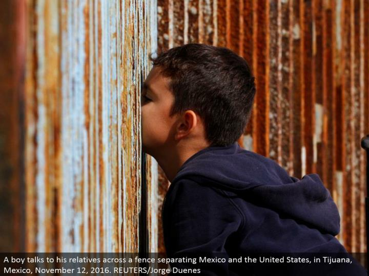 A kid converses with his relatives over a fence isolating Mexico and the United States, in Tijuana, Mexico, November 12, 2016. REUTERS/Jorge Duenes