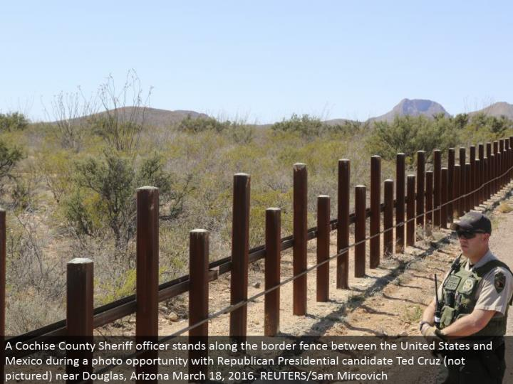 A Cochise County Sheriff officer remains along the fringe fence between the United States and Mexico amid a photograph opportunity with Republican Presidential hopeful Ted Cruz (not envisioned) close Douglas, Arizona March 18, 2016. REUTERS/Sam Mircovich