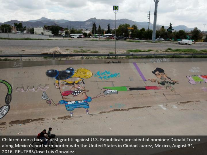 Children ride a bike past spray painting against U.S. Republican presidential chosen one Donald Trump along Mexico's northern fringe with the United States in Ciudad Juarez, Mexico, August 31, 2016. REUTERS/Jose Luis Gonzalez