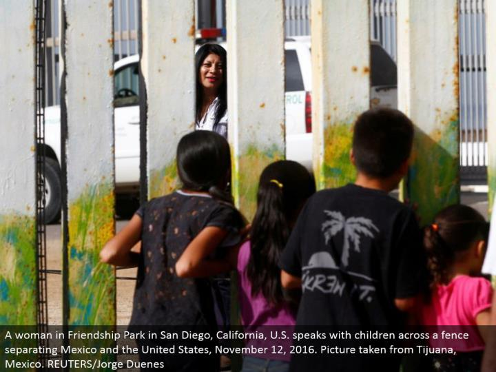 A lady in Friendship Park in San Diego, California, U.S. talks with kids over a fence isolating Mexico and the United States, November 12, 2016. Picture taken from Tijuana, Mexico. REUTERS/Jorge Duenes