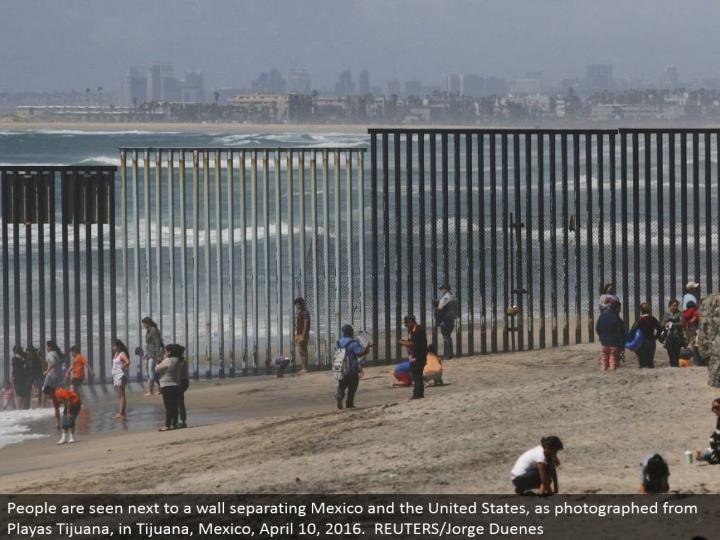 People are seen alongside a divider isolating Mexico and the United States, as shot from Playas Tijuana, in Tijuana, Mexico, April 10, 2016. REUTERS/Jorge Duenes